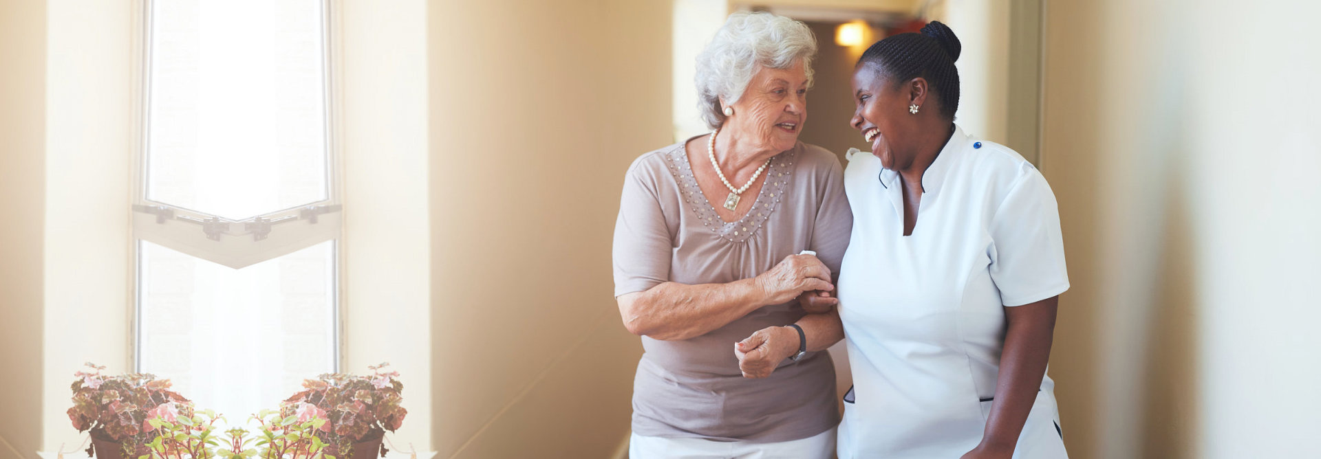 caregiver and old woman happily walking in the aisle