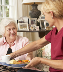 caregiver preparing meal for old woman