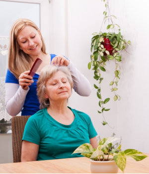 caregiver combing hair of old woman