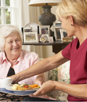 caregiver preparing meal to her patient